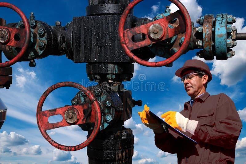 Tekniker Writing On Clipboard på oljabrunnen mot molnig blå himmel i bakgrund royaltyfria foton