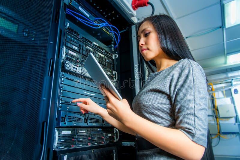 Teknikeraffärskvinna i rum för nätverksserver fotografering för bildbyråer
