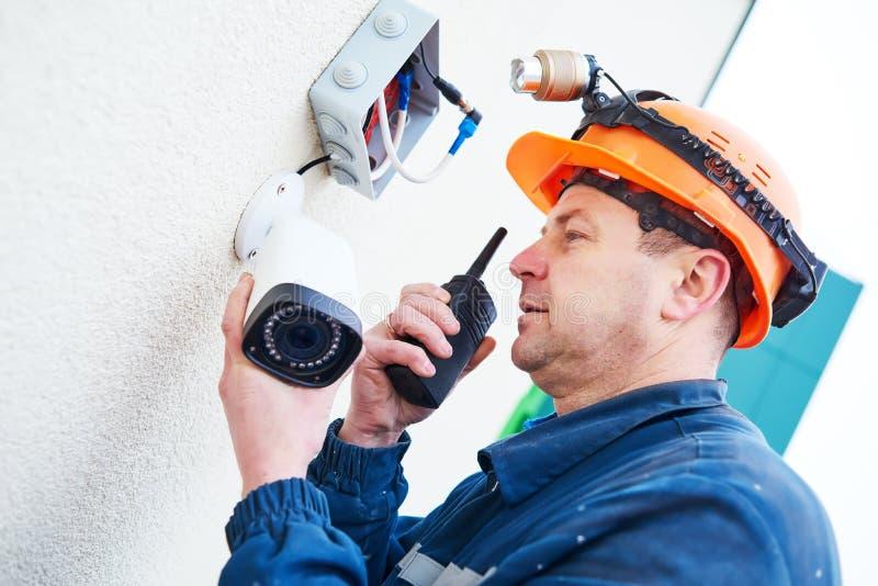 Teknikerarbetare som installerar den videopd bevakningkameran på väggen royaltyfria foton