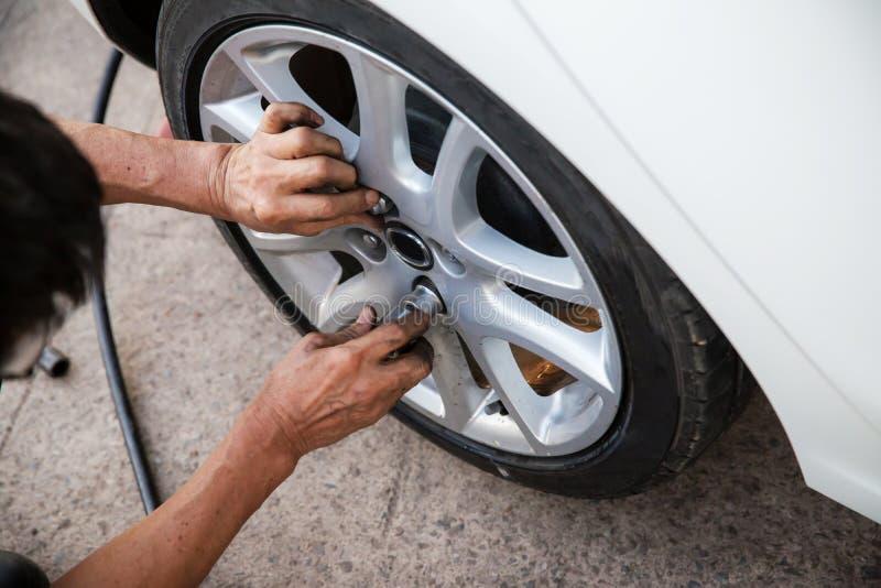 Teknikerarbetaren skruvar hjulbulten med en manuell skiftnyckel underhåll och kontrollbilbegrepp övre kontroll och fixandeveh arkivfoto