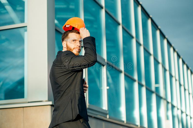 Teknikerarkitektbyggmästaren ser konstruktion av strukturen som bär en hjälm arkivfoton