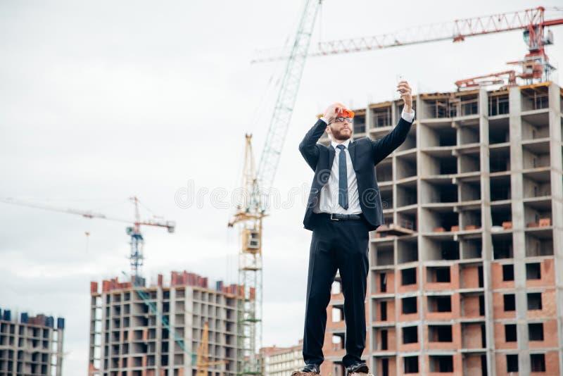 Teknikerarkitektbyggmästaren ser konstruktion av strukturen som bär en hjälm royaltyfri fotografi