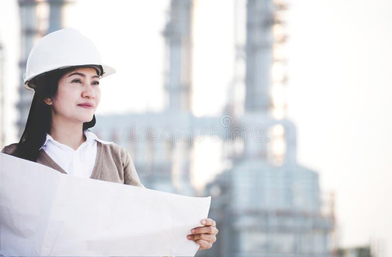 Teknikerasia kvinna med den hårda hatten som rymmer det blåa trycket pappers- se kontrollerande bort framsteg på konstruktionskra royaltyfri fotografi