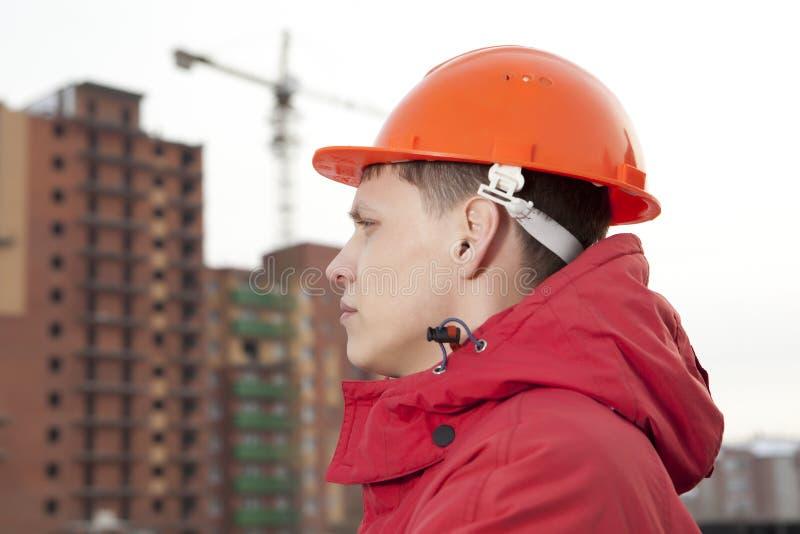 Teknikerbyggmästare i hjälm på konstruktionsplatsen royaltyfri bild