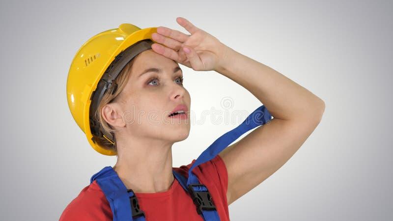 Teknikerbyggnadsarbetarekvinna som fascineras av skalan av konstruktion på lutningbakgrund royaltyfri foto