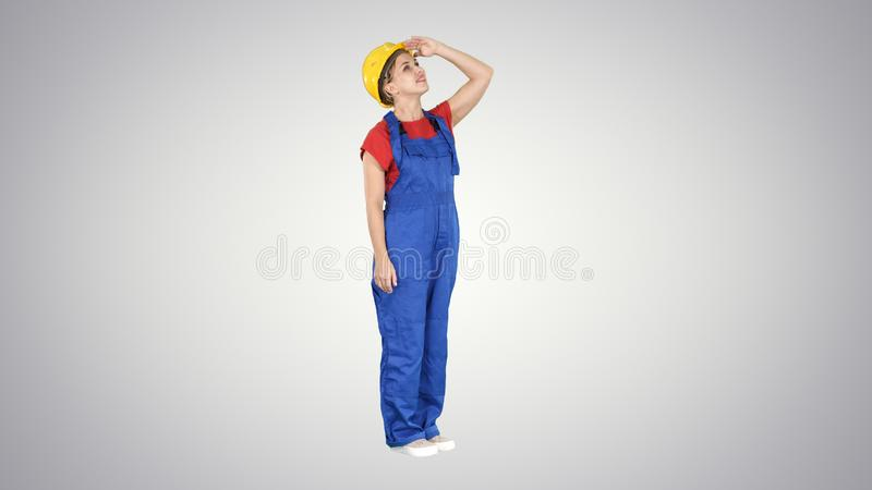 Teknikerbyggnadsarbetarekvinna som ser upp på en byggnad eller statistik eller graf som slutligen skrattar på lutning royaltyfria bilder