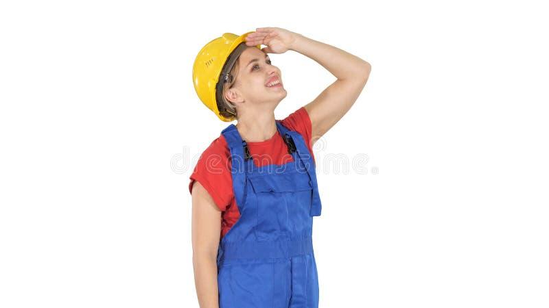 Teknikerbyggnadsarbetarekvinna som ser upp på något som förbluffar och skrattar på vit bakgrund royaltyfri bild