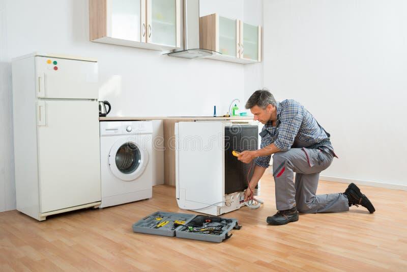 TeknikerChecking Dishwasher With Digital Multimeter royaltyfri fotografi