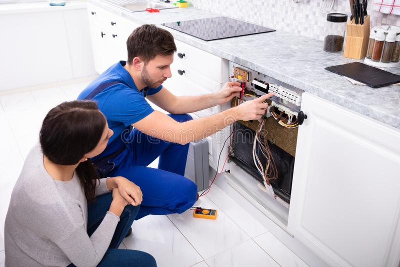 TeknikerChecking Dishwasher With Digital Multimeter arkivbilder