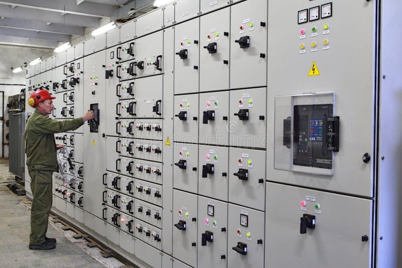 Teknikerelektrikeren kopplar switchgearutrustning royaltyfri foto