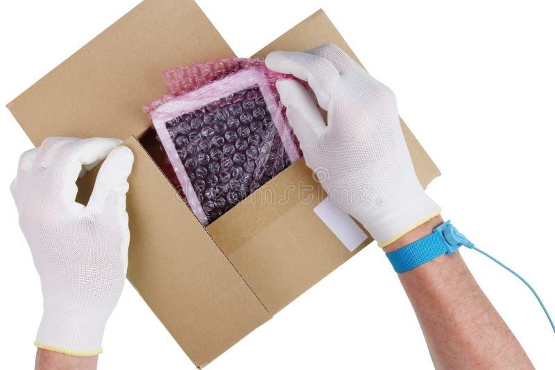 Teknikeren i antistatiska handskar tar ut en minnestavlareservdelmedeltal fotografering för bildbyråer