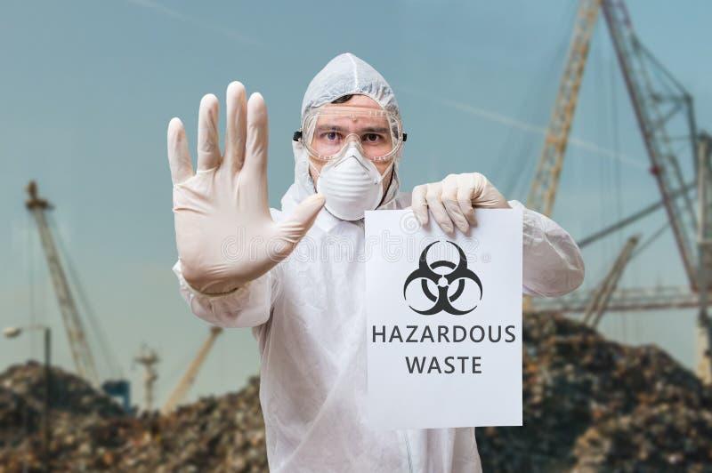 Teknikeren i overall varnar i nedgrävning av sopor om farlig avfalls royaltyfri fotografi