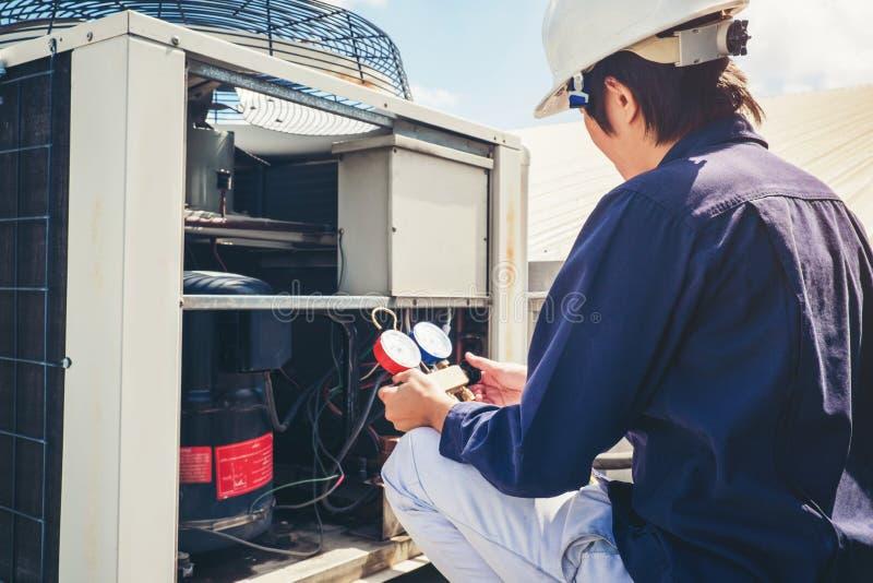 Teknikeren kontrollerar luftkonditioneringsapparaten royaltyfria bilder