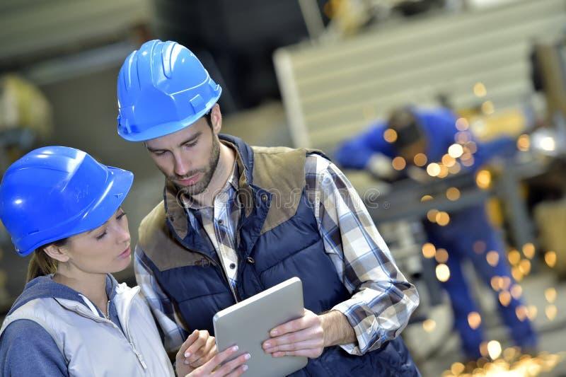 Teknikerer i den metallurgiska fabriken som arbetar på den digitala minnestavlan royaltyfria foton