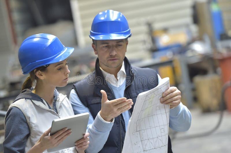 Teknikerer i en metallurgisk fabrik som diskuterar royaltyfri bild