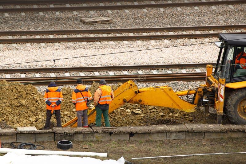 Teknikerer och järnväg arbetare reparerar spåret genom att använda en grävskopa Infrastruktur av transportkommunikationsknutpunkt royaltyfri fotografi