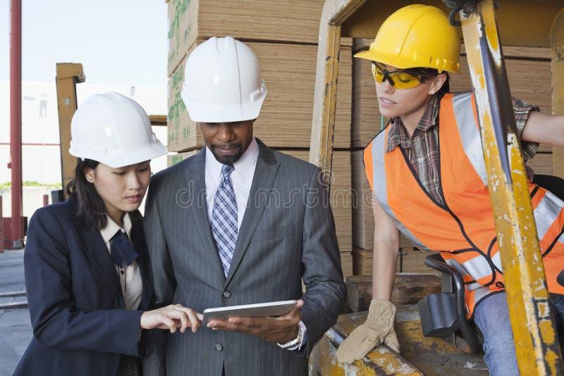 Teknikerer och kvinnlig industriarbetare som ser minnestavlaPC arkivbild