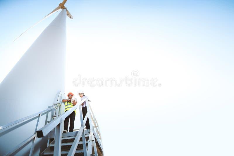 Teknikerer och vindturbiner royaltyfri foto