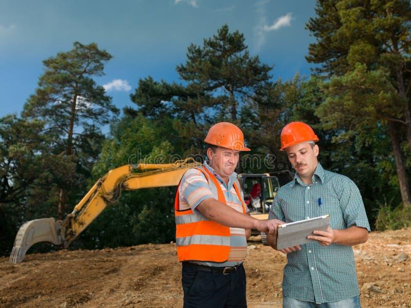 Teknikerer som diskuterar på konstruktionsplats arkivbilder
