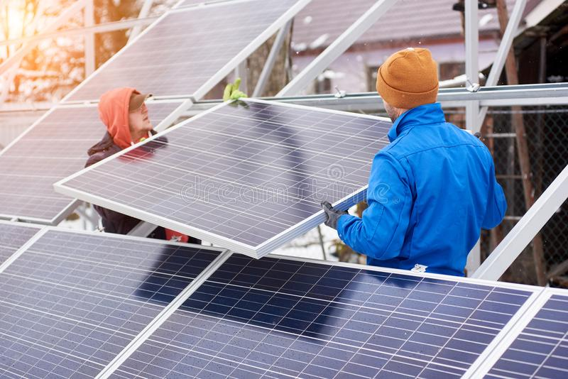 Teknikerer som installerar solpaneler i vinter royaltyfri foto
