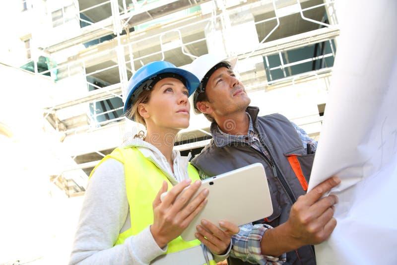 Teknikerer som kontrollerar plan på konstruktionsplats arkivfoto