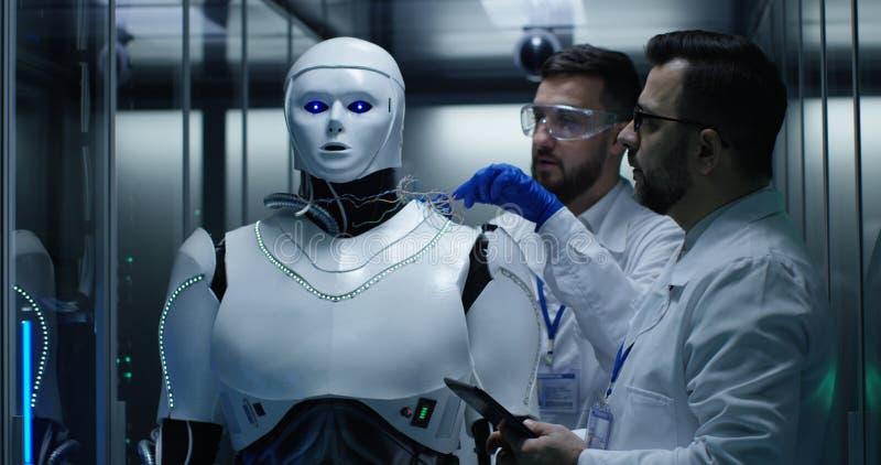 Teknikerer som testar på robotstyrning inom laboratoriumet royaltyfri bild