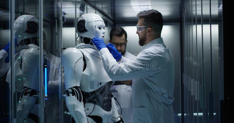 Teknikerer som testar på robotstyrning inom laboratoriumet royaltyfria bilder