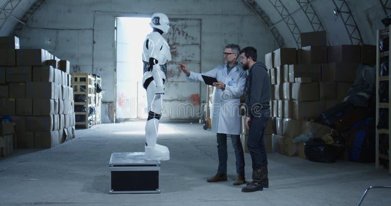 Teknikerer som testar roboten i ett lager royaltyfri bild