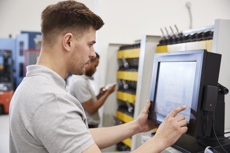 Teknikerer som väljer hjälpmedel för bruk på maskineri i fabrik arkivfoton