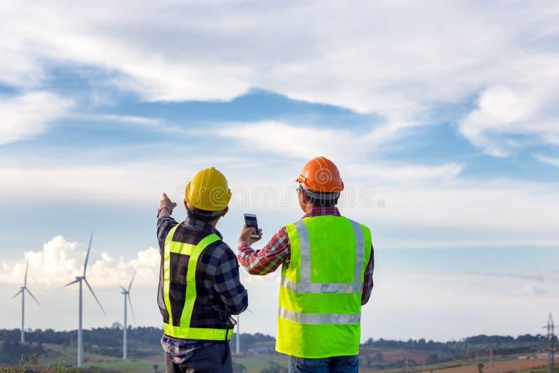 Teknikererna som står utomhus- grön energi för granskningsvindturbiner royaltyfri foto