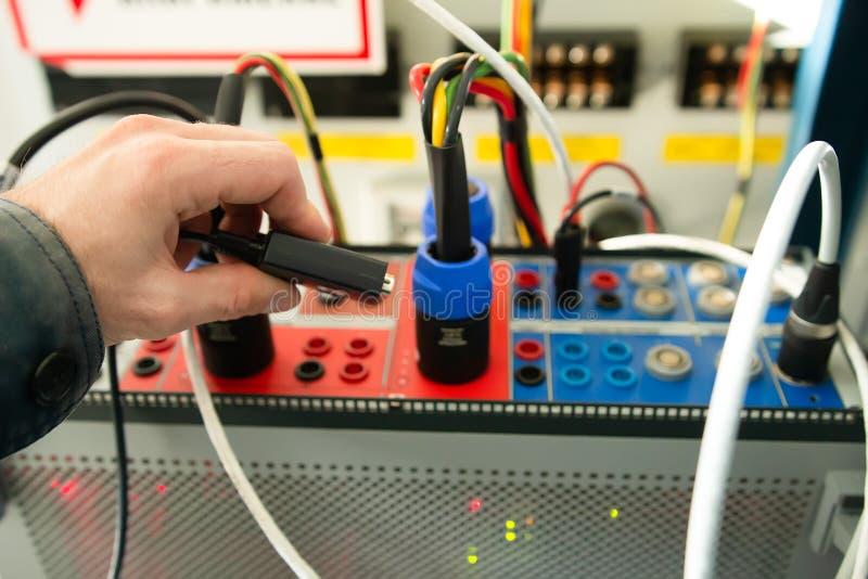 Teknikerförbindande provpropp till den elektriska apparaten för att testa relän arkivbild
