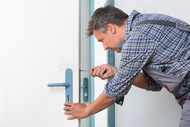 TeknikerFixing Lock In dörr med skruvmejsel arkivfoto