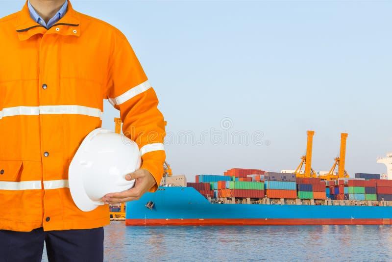 Teknikerhamnarbetare som in bär det säkerhetslaget och innehavet en hjälm för royaltyfri bild