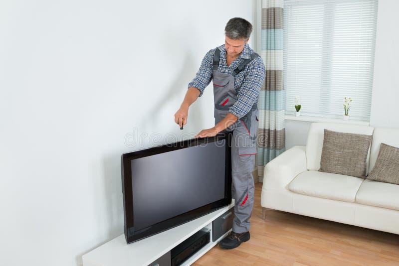 TeknikerInstalling Television At hem royaltyfri fotografi