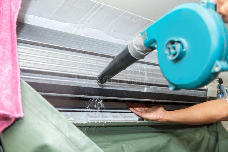 Teknikermannen torkar upp och dammar av lokalvårdluftkonditioneringsapparatfilter w arkivfoto