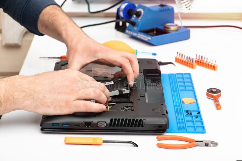 Teknikern demonterar detaljerna av en bruten b?rbar dator f?r reparation arkivfoton