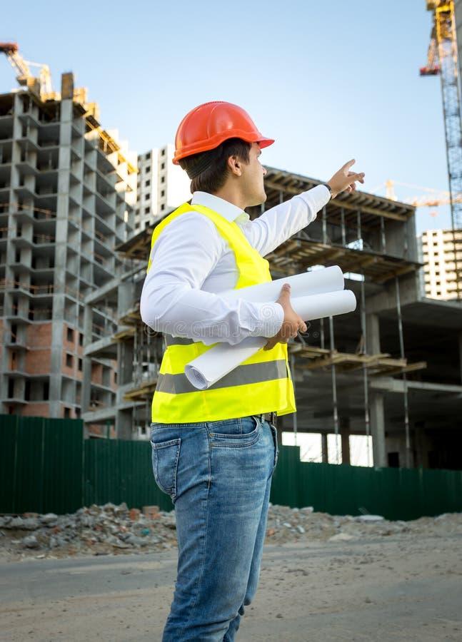 Teknikern i hardhat och säkerhet klår upp kontrollera byggnadsplatsen arkivfoto