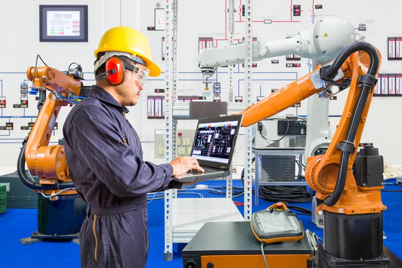 Teknikern installerar och robotic provningsbransch i tillverkning royaltyfria bilder