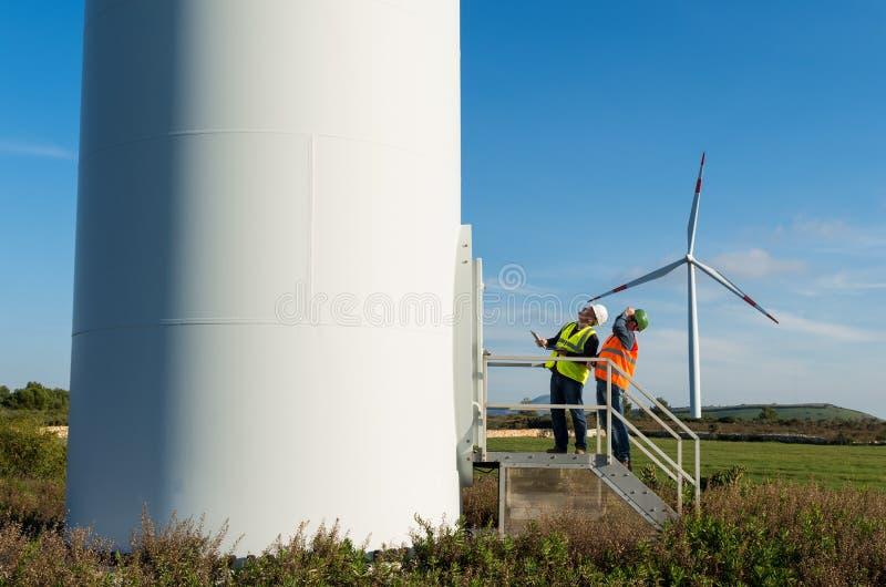 Teknikern och geologen konsulterar nästan vindturbiner i bygden royaltyfria bilder