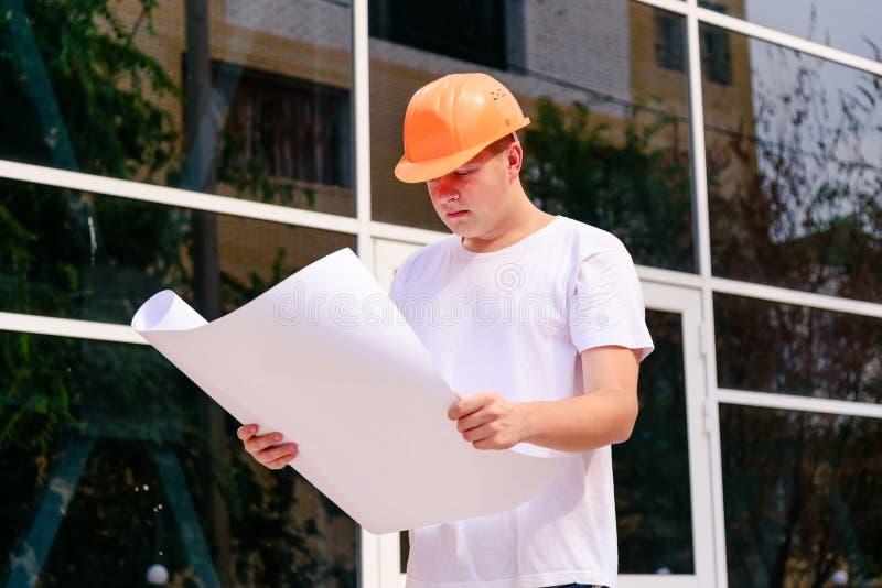 Teknikern på byggandeplatsen i en orange hjälm och en vit t-skjorta rymmer planet av en stroitelsv i hand Kontroll av royaltyfria bilder