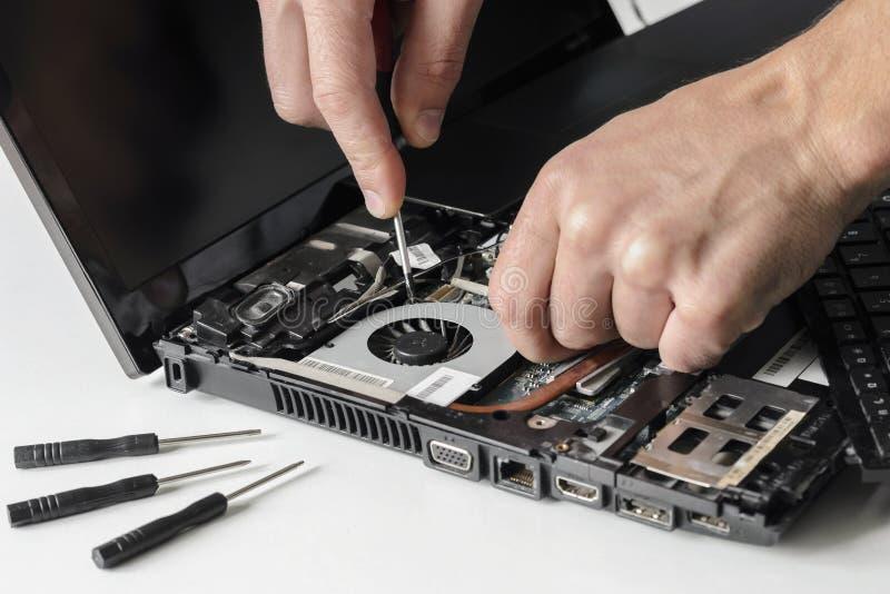 Teknikern reparerar bärbara datorn, dator Installerar utrustningCPUen fotografering för bildbyråer