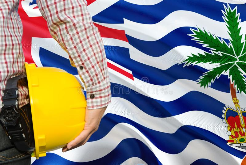 Teknikern rymmer den gula säkerhetshjälmen med att vinka bakgrund för flaggan för det brittiska Indiska oceanenterritoriet Konstr royaltyfri foto