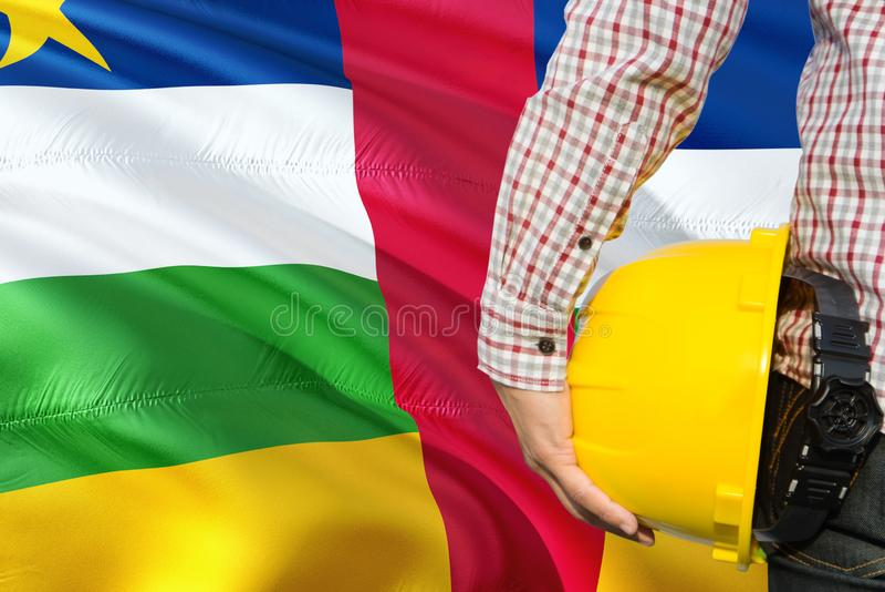 Teknikern rymmer den gula säkerhetshjälmen med att vinka Centralafrikanska republiken flaggabakgrund Konstruktions- och byggnadsb royaltyfri fotografi