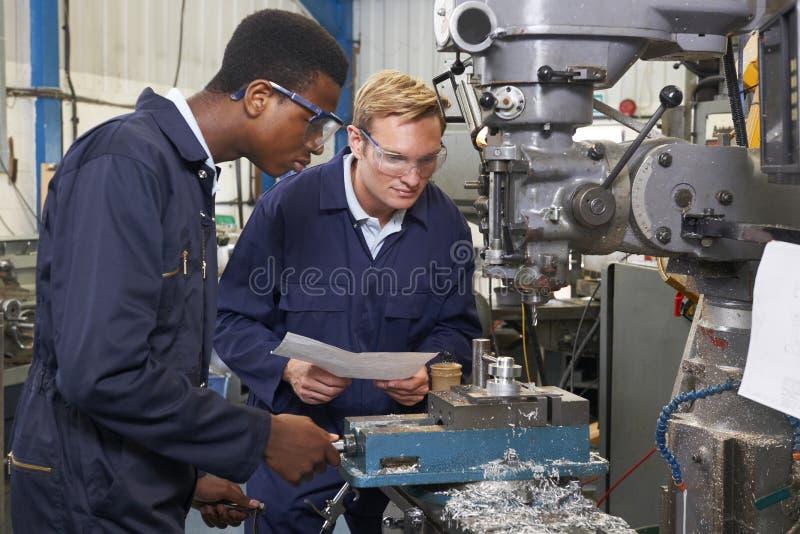 Teknikern Showing Apprentice How som ska användas, borrar in fabriken fotografering för bildbyråer