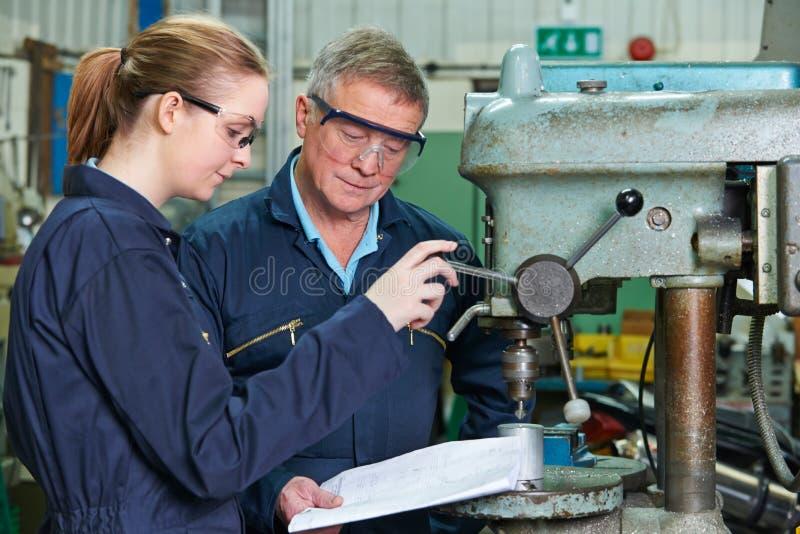 Teknikern Showing Female Apprentice hur man använder borrar in fabriken arkivbilder