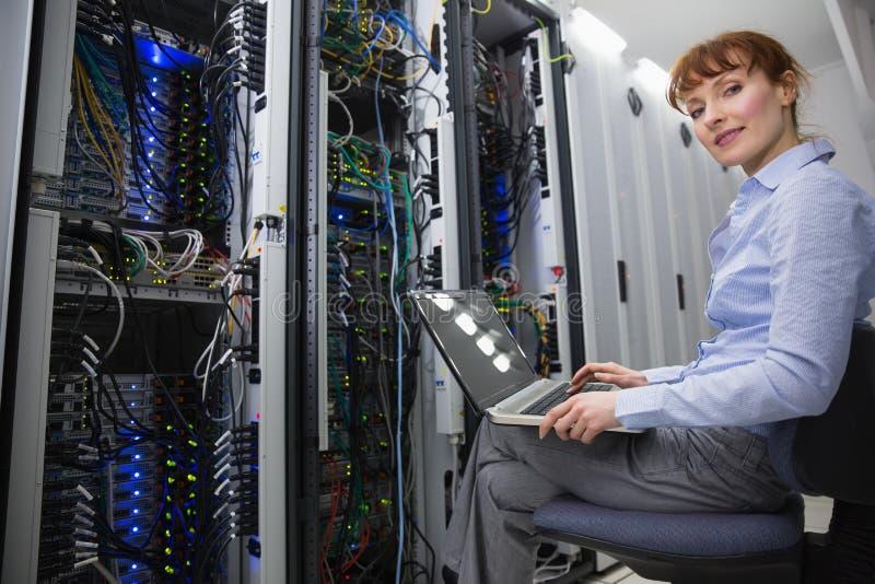 Teknikersammanträde på svängtappstol som använder bärbara datorn för att diagnostisera serveror royaltyfri bild