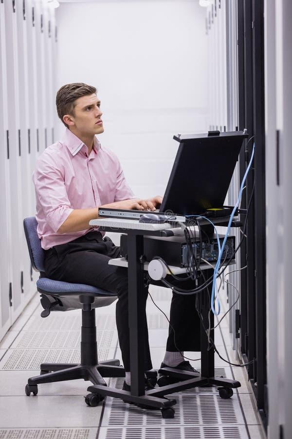 Teknikersammanträde på svängtappstol som använder bärbara datorn för att diagnostisera serveror royaltyfria foton