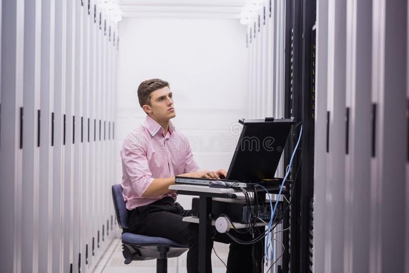 Teknikersammanträde på svängtappstol som använder bärbara datorn för att diagnostisera serveror arkivbild