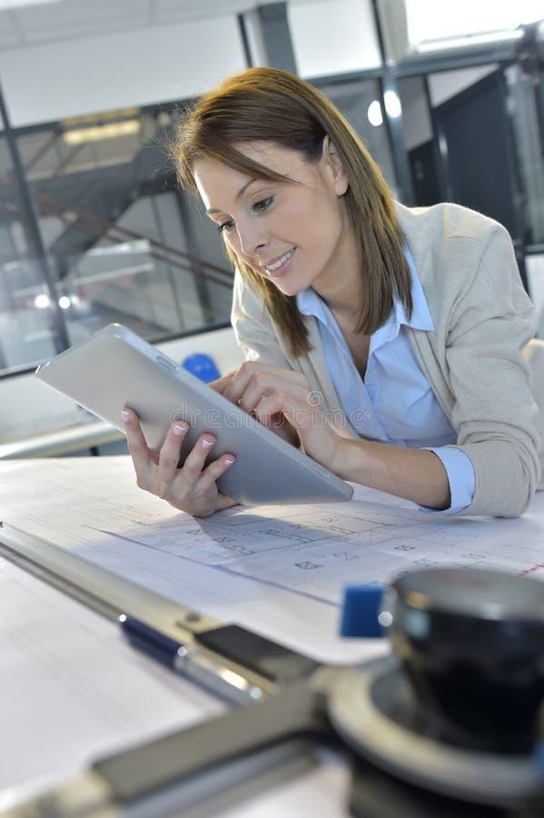 Teknikerworkin för ung kvinna på kontoret genom att använda en minnestavla arkivbild