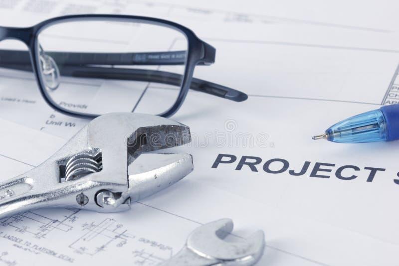 Teknikprojekt som drar dokument med skiftnyckeln, glasögon, penna royaltyfria foton